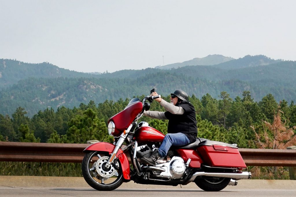A motorcyclist driving on a highway near a forest in Keystone, South Dakota