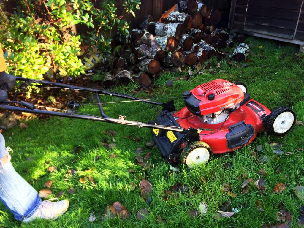 A person mowing the lawn in fall, while also mulching leaves with a lawn mower