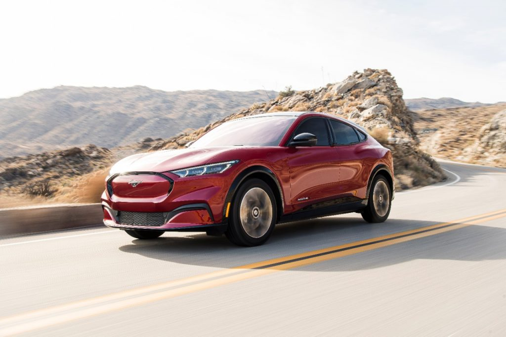 A red 2021 Ford Mustang Mach-E driving, the Mach-E is an electric SUV in direct competition with the Tesla Model Y