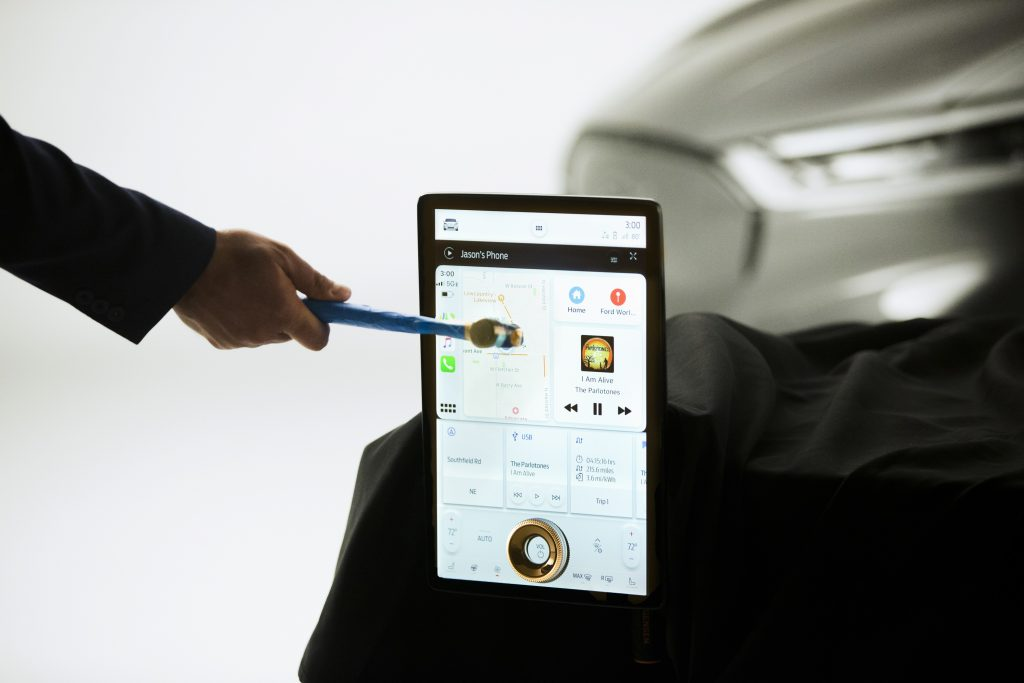 A man takes a hammer to the touchscreen on the Mach E