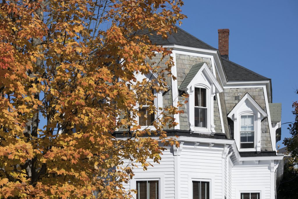 A Clapboard Home in Newport, Rhode Island, USA with fall leaves in front of it