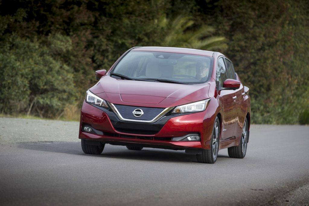 The front end of a red 2018 Leaf on a forested backroad
