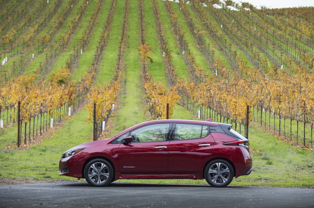 A red Nissan Leaf photographed in profile in a field
