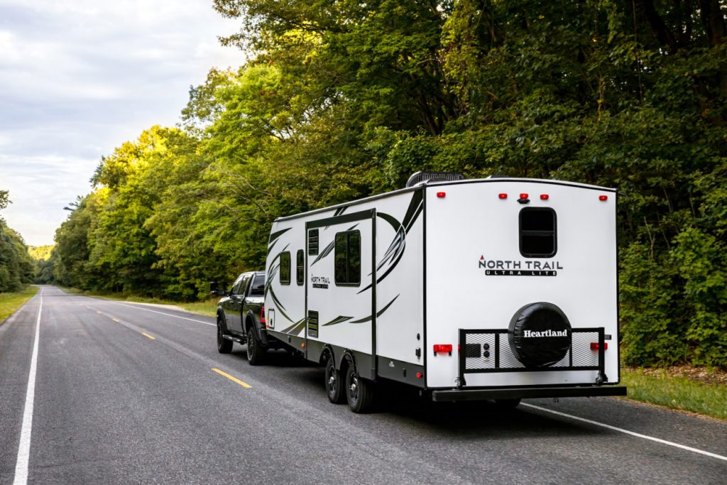 a North Trail travel trailer being pulled on a road in the forest