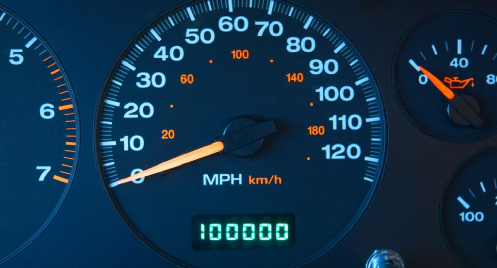 An automobile odometer with 100000 miles shown.
