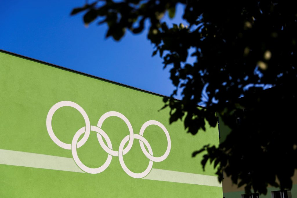 White Olympic rings painted on a green building with a blurred tree in the foreground to the left.