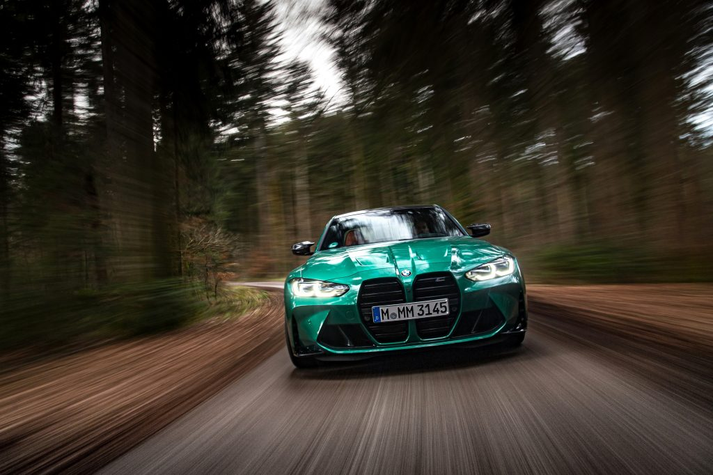 The new BMW M3 luxury sports car on a forested road