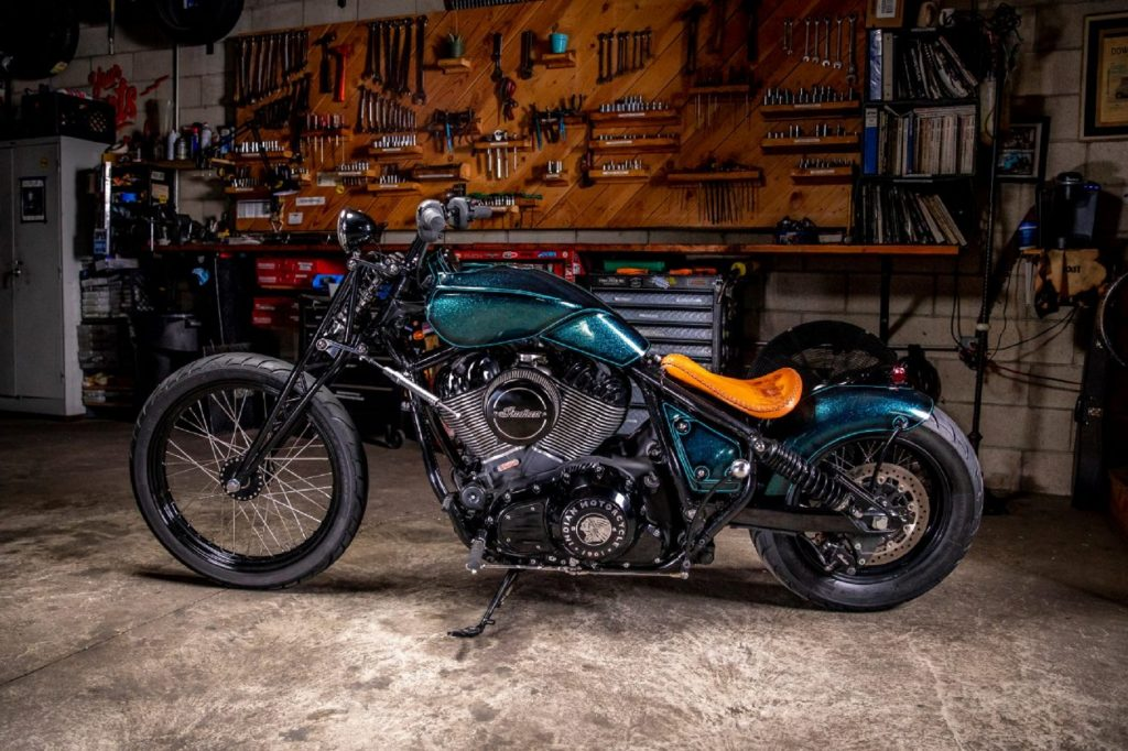 The side view of Paul Cox's and Keino Sasaki's metallic-green custom 2022 Indian Chief in a garage