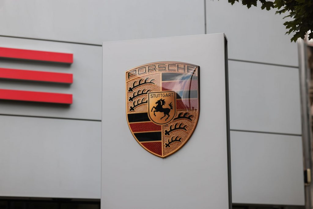 A Porsche sign in front of a building with the logo.