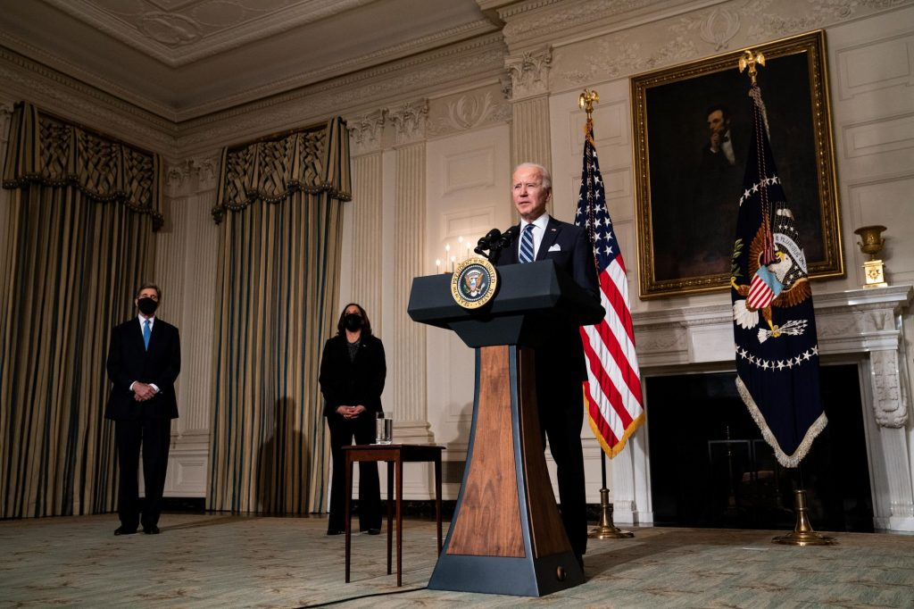 President Joe Biden speaking about climate change at the White House as John Kerry and Kamala Harris stand at his side