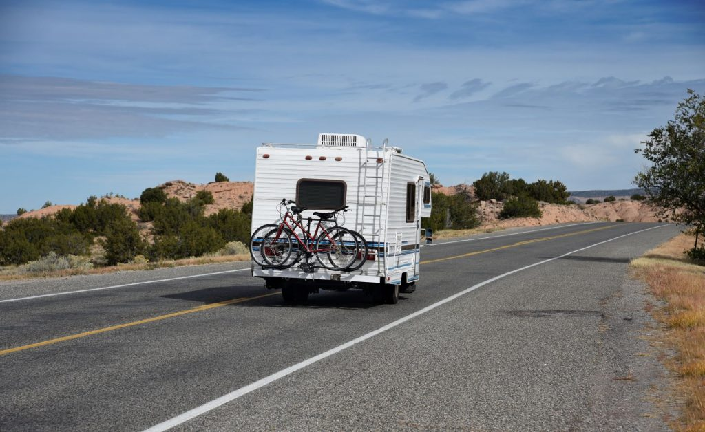 A moving RV with bikes on the back driving in New Mexico