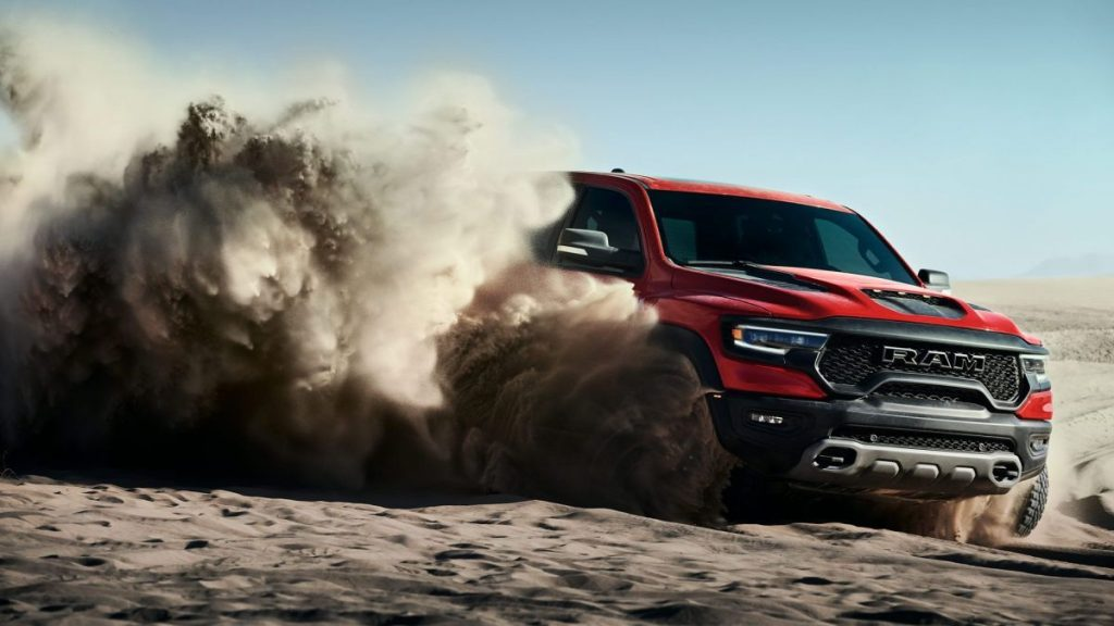 This is a publicity photo of a red RAM TRX throwing up dust. Read about the Rise of The Supertruck: Brabus, Tesla, and Hummer Lead This New Exotic Truck Class