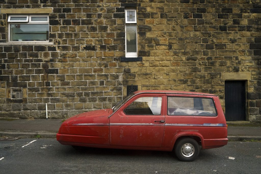 Reliant Robin parked on the side of the road in England. This little car is related to the Bond Bug used to create Luke Skywalker's Landspeeder