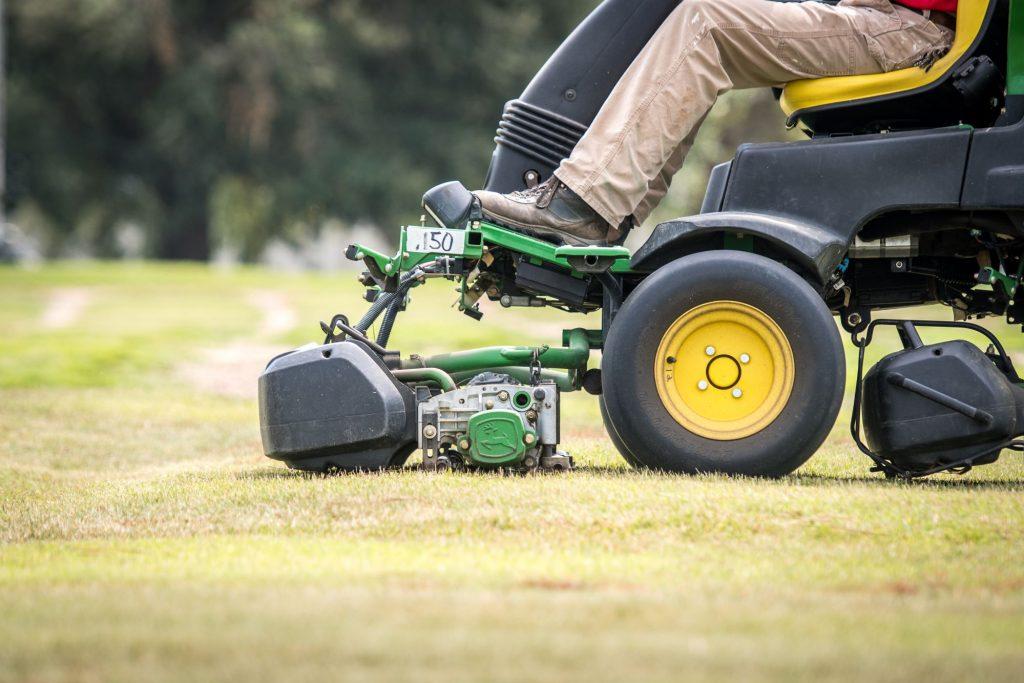 A man operating a riding lawn mower to cut grass in Tifton, Georgia