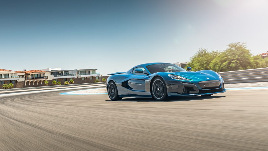 A turquoise-blue Rimac Nevera electric supercar driving on a track on a sunny day