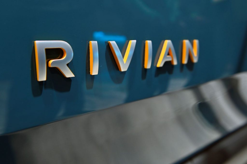 Rivian spelled out in metal letters on the back of a dark teal piece of metal.