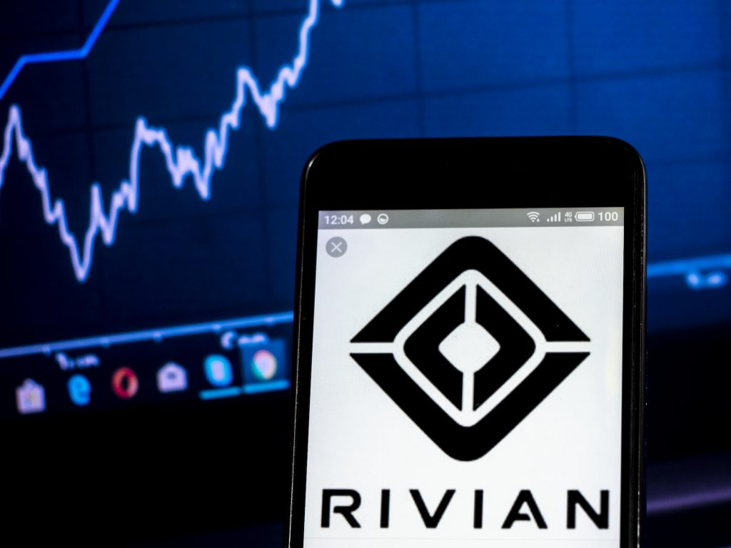 The Rivian logo is displayed on a smartphone with a blue line graph in the background