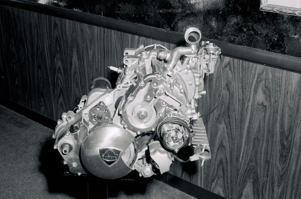 A black and white picture of a rotary engine with a wooden backdrop.