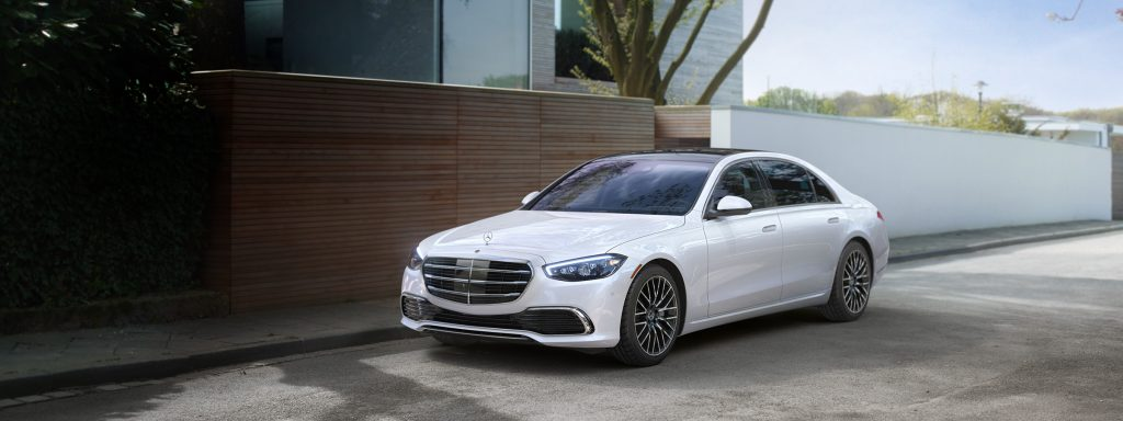 A white 2021 Mercedes S-Class parked outside of a house.