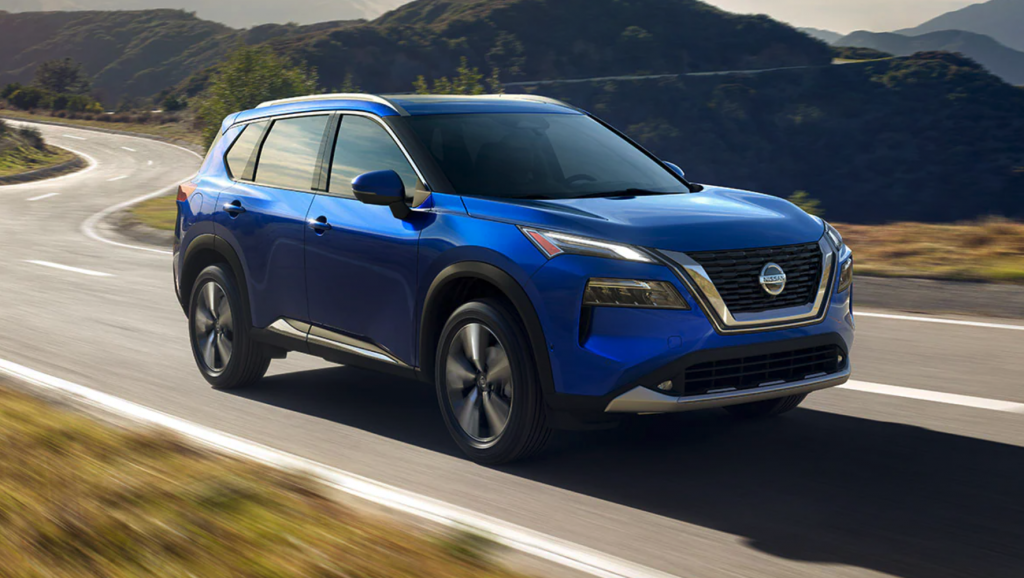 A blue 2021 Nissan Rogue driving on the road