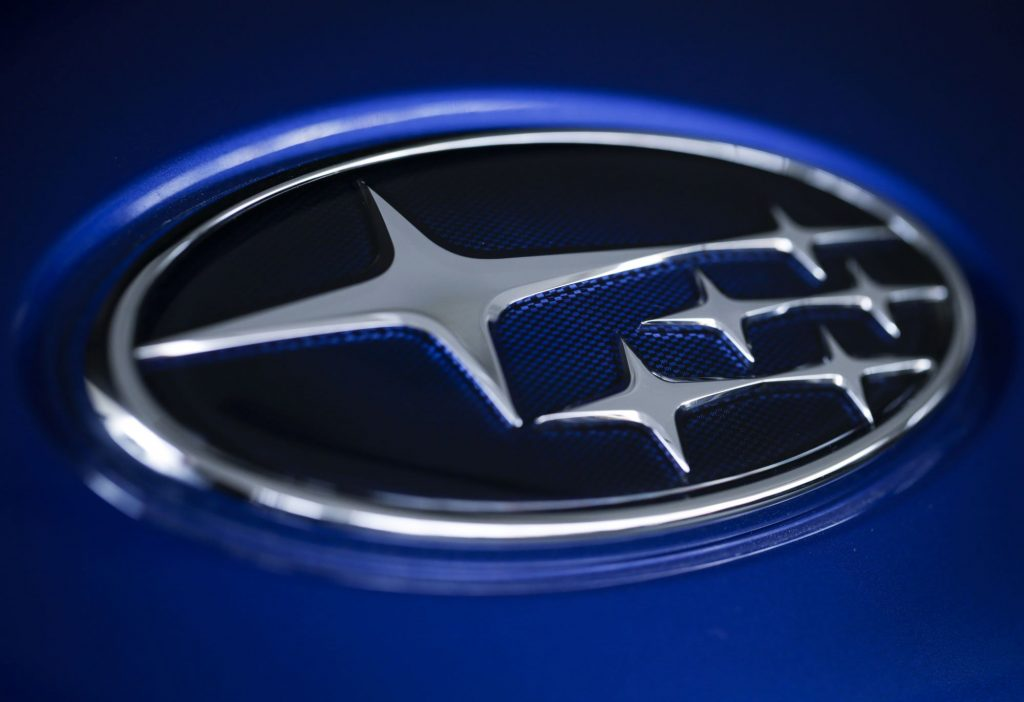 A dark blue Subaru logo with silver accents against a lighter blue background.