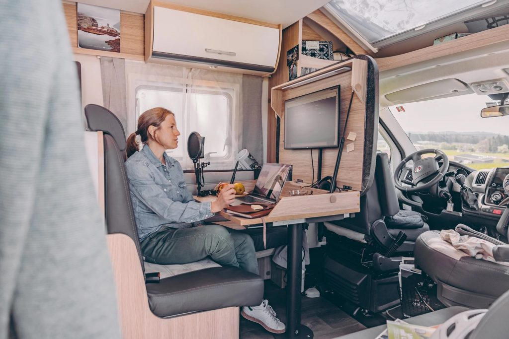 Woman sits at the fold-out work station on the ultimate work remote camper rig