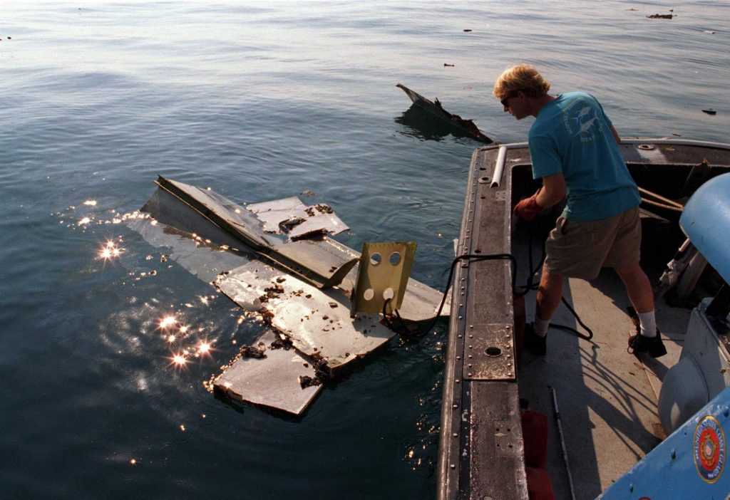 In the aftermath of the crash of TWA Flight 800, crew members of the Coast Guard cutter Jupiter load pieces of the jetliner on to the ship's deck on July 18, 1996. A section of the plane's tail can be seen in the water.