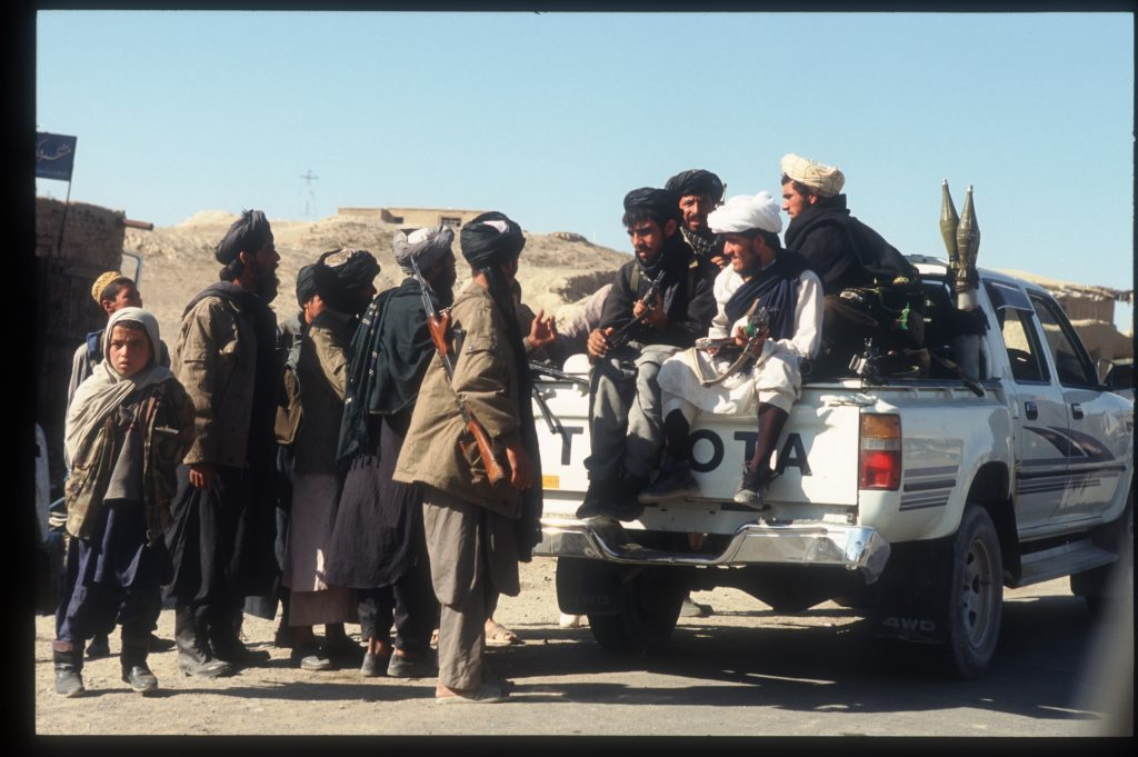 Taliban loaded into the back of an old Toyota pickup truck
