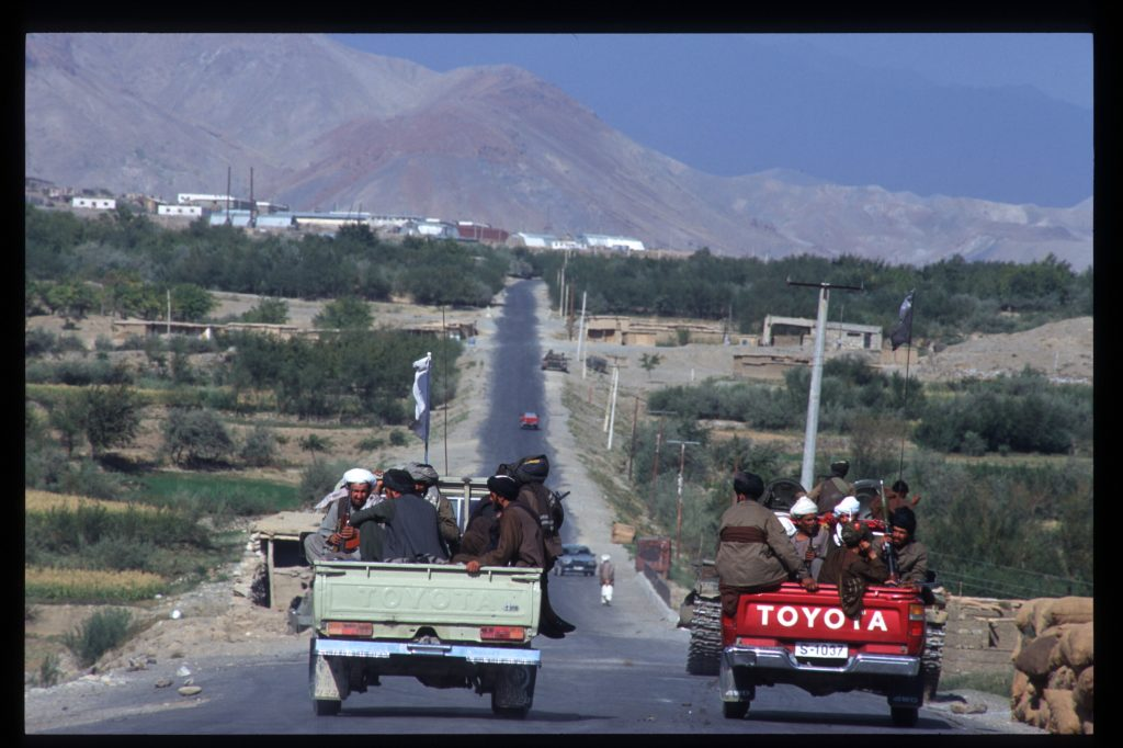 Taliban forces riding down the road in Toyota pickup trucks