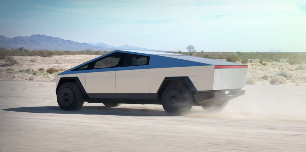 This is a publicity photo of a silver Tesla Cybertruck driving through the desert. Read about the Rise of The Supertruck: Brabus, Tesla, and Hummer Lead This New Exotic Truck Class