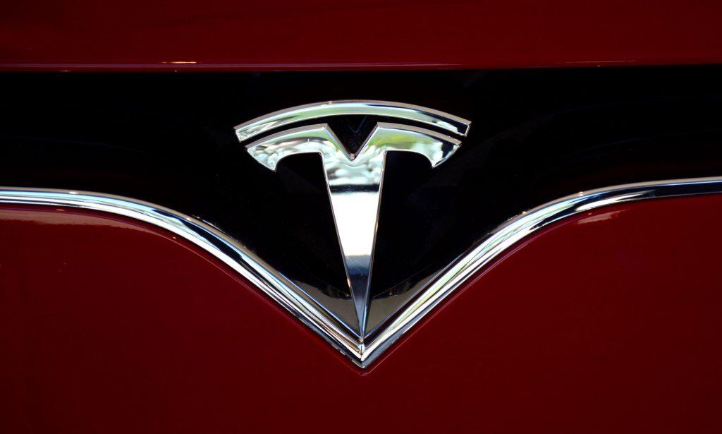 A chrome Tesla logo on a black background on a red car.