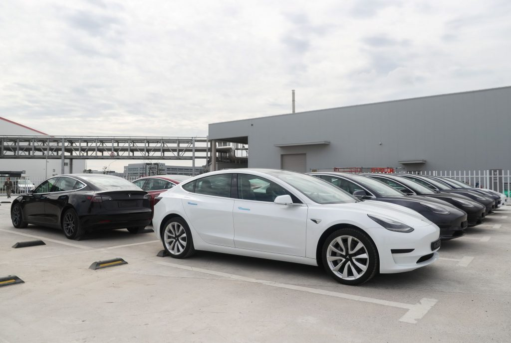 Tesla Model 3 vehicles parked outside of a Tesla factory in Shanghai, China