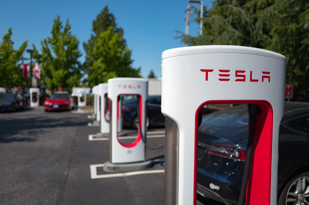 A row of white Tesla chargers with trees in the background.