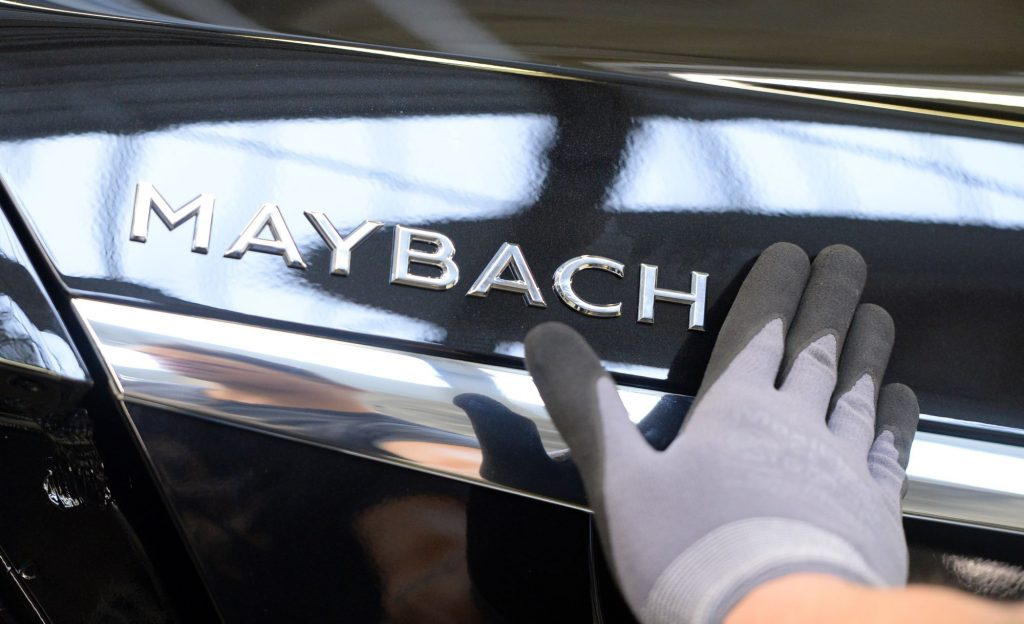 Maybach printed in all capital letters on the back if the Mercedes Maybach with a gloved hand on the left.