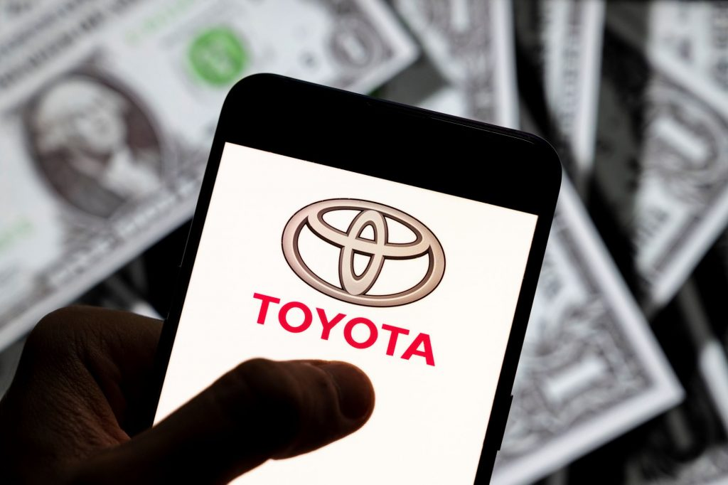 The affordable car Toyota logo on a smart phone with dollar bills in the background.