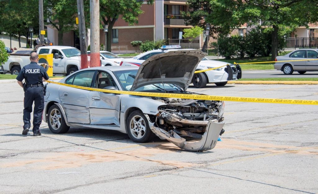 A police officer standing next to a totaled vehicle surrounded by police tape