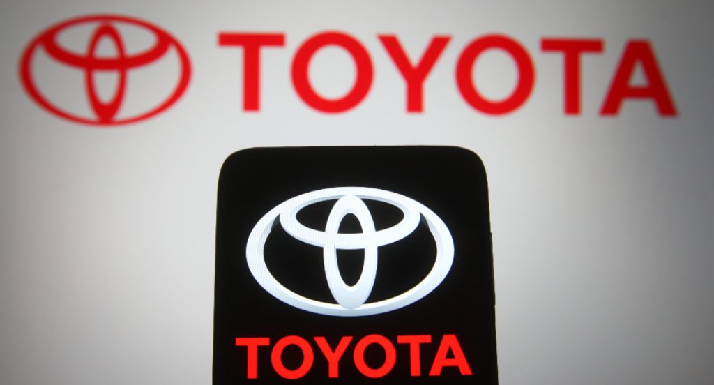 In this photo illustration, a Toyota logo seen displayed on a smartphone and a pc screen.