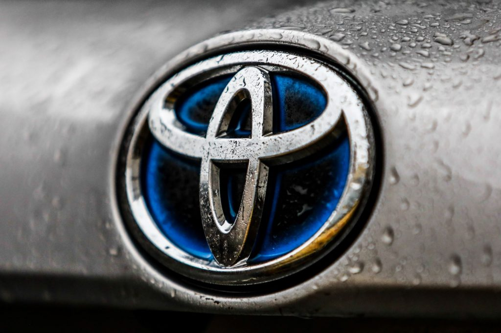 A chrome Toyota logo with a blue center on a silver car with water drops.