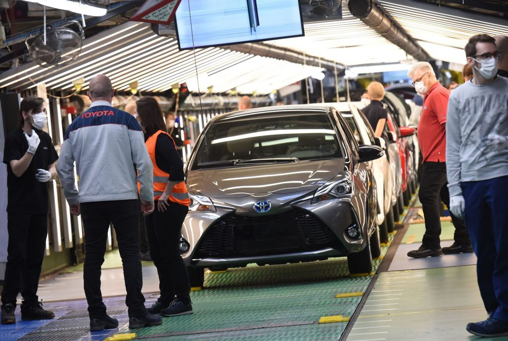 Toyota Manufacturing plant with people standing around assembling cars with multiple cars coming down the line.