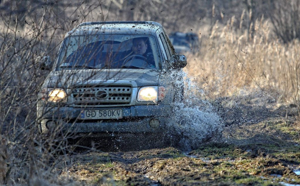 A pickup truck driving through mud during an off-road race
