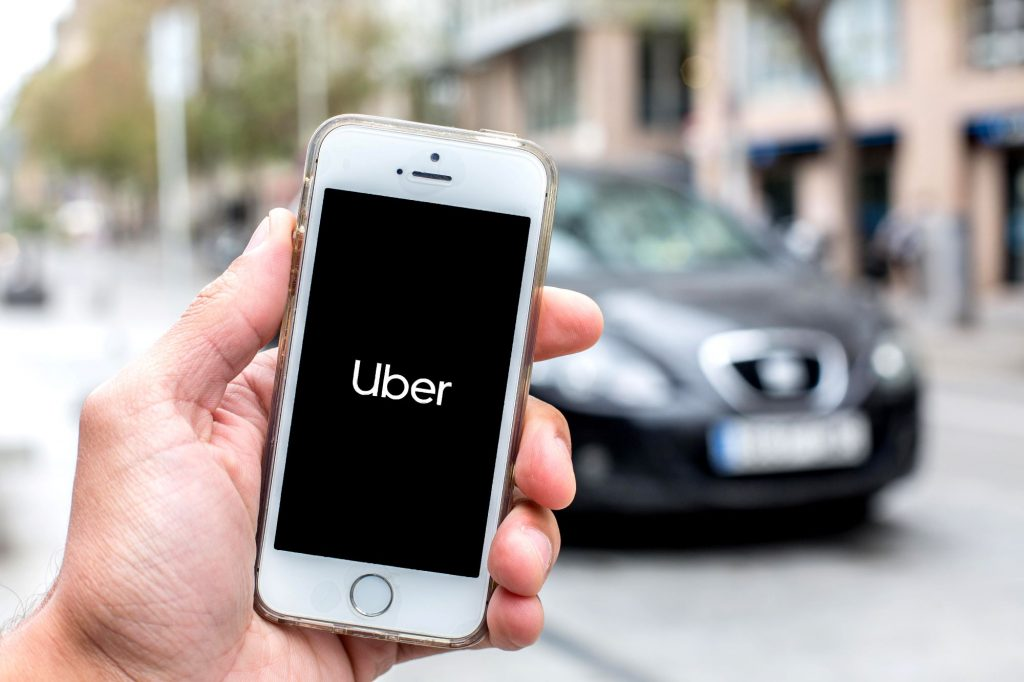 The Uber ride-share app open on a smartphone as the driver and ride arrive to pick up a passenger