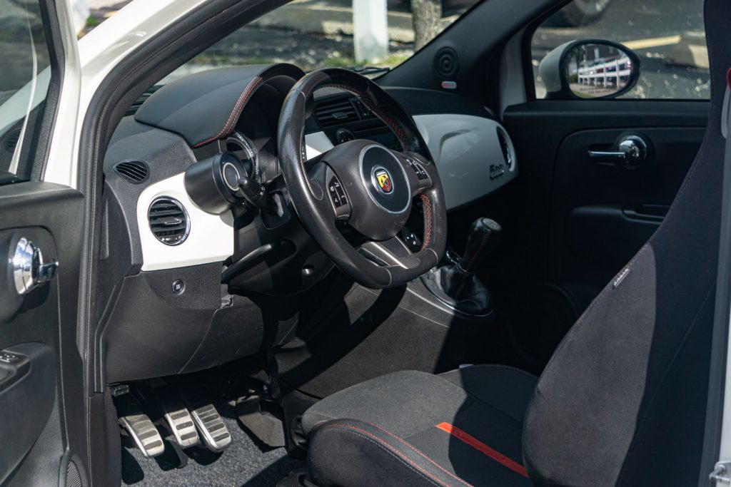 The black-and-red seats and white dashboard of a white used 2013 Fiat 500 Abarth