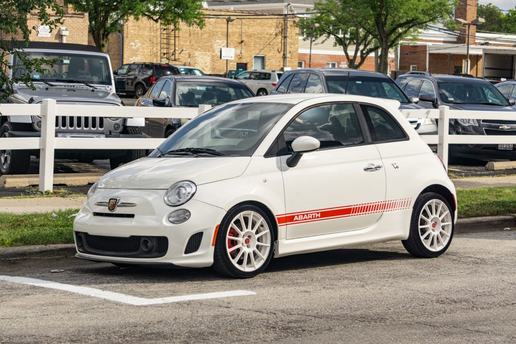 The author's white-and-red 2013 Fiat 500 Abarth on a city street