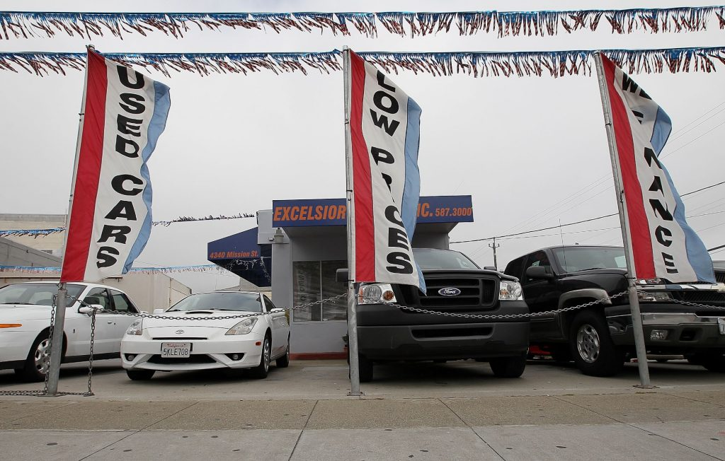 A used cars lot with flags and used cars.