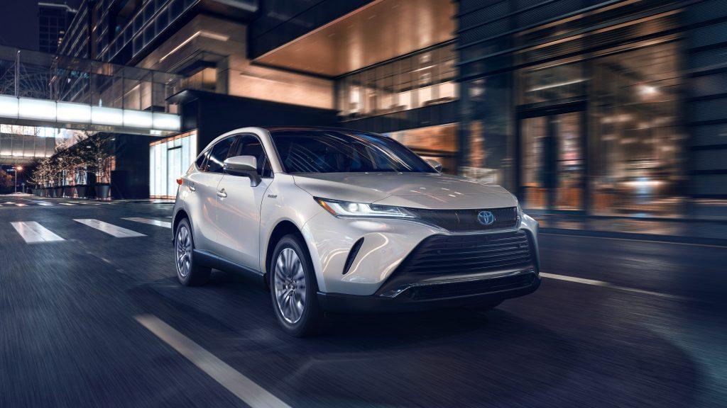 A white 2021 Toyota Venza driving through a dark city