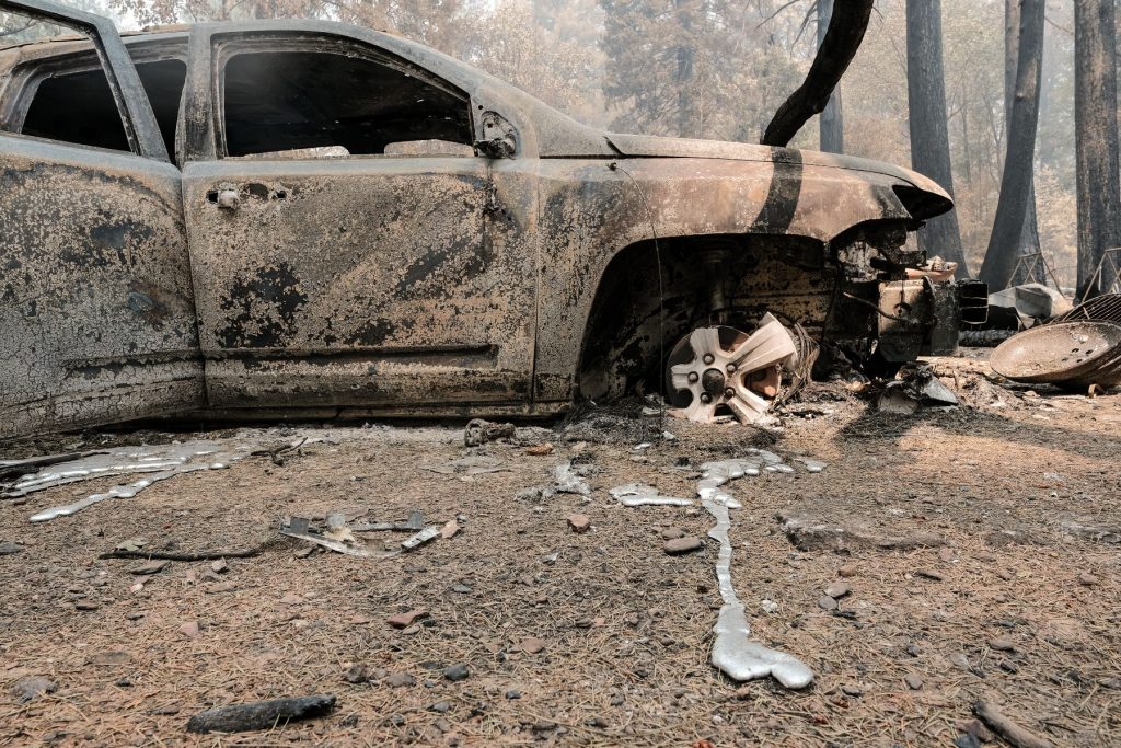 A burned vehicle and destroyed forest road from the Dixie Fire worsened by climate change