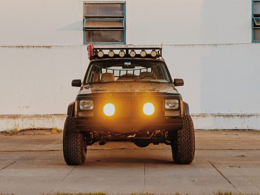Jeep Cherokee front grill with added lights on a 90s overlander