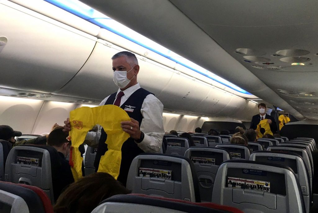 Flight attendants checking safety precautions in an airplane cabin before takeoff