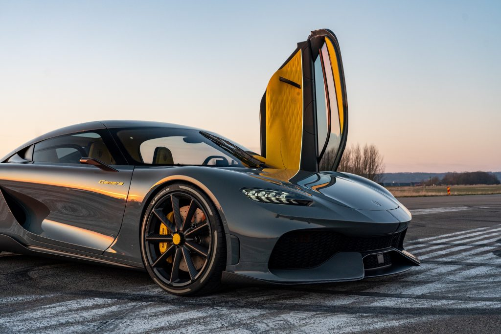 A grey 2021 Koenigsegg Gemera sits on a runway at sunset with the driver's door sticking straight up into the air
