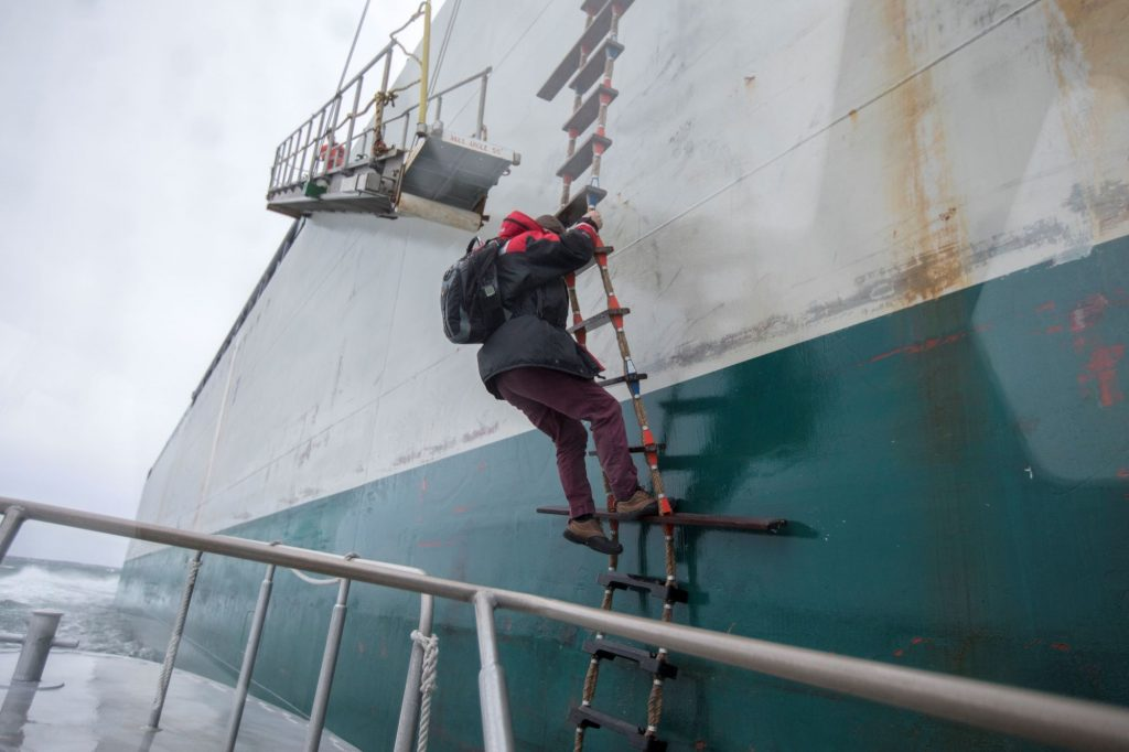 A harbor pilot climbing a boat ladder in Boston Harbor of Boston, Massachusetts